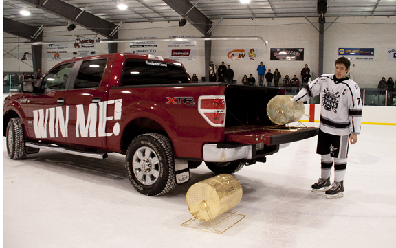 AND THE WINNER IS: Richard Gladue was the lucky winner of a brand new truck courtesy of PineRidge Ford in Meadow Lake. Both the truck and a 50-50 prize were awarded following a yearlong raffle to raise money for the newly constructed arena at Flying Dust First Nation. More than 400 fans packed the arena Dec. 13 to witness midget AAA action between the Battleford Stars and the Beardy's Blackhawks. Between periods, Battleford player Robin Yew (pictured here) drew the winning ticket. The winner of the 50-50 draw was Danny Mantyka.