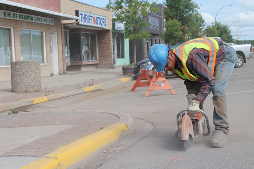 City workers were busy last week preparing Centre Street for new street lights. The work is a continuation of a project started last fall. After asphalt and bricks along the sidewalk are removed, SaskPower will move in to complete the job. Here, city labourer Kane Shkopich saws through asphalt along Centre Street.