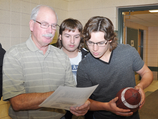Carpenter High Schools Spartans players Dean Poitras (centre) and Blaik Esau (right), along with former CHS player Maurice Demmans, take a closer look at a photo of the 1963 CHS football team that also faced Indian Head for the provincial championship.