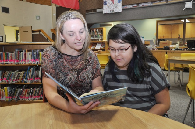 Jubilee Elementary School teacher Andrea Pearson reads a book with Grade 4 student Jada Roberts.