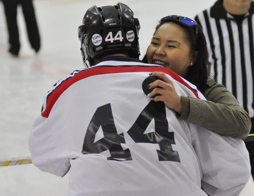 Patuanak Pats player and nephew of Abe Apesis, Jonathan Apesis, receives a hug from Kayleen Apesis, Abe Apesis' daughter.