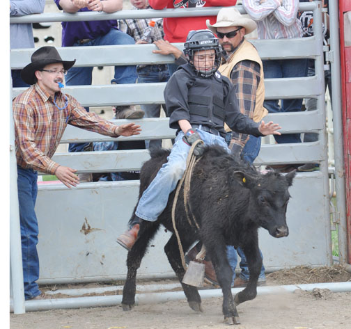 Meadow Stampede Association volunteers Terry Villeneuve (left) and Mark Campbell look on as Ricky Lafond attempts to maintain his balance during Saturday's calf and steer riding clinic at the Meadow Lake Stampede Grounds.
