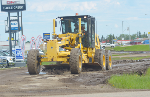 A grader is used to smooth out the west service road adjacent to Highway 4 last week. Residents have been concerned as of late with the condition of many streets throughout the community.