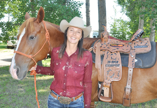 Rapid View area resident Nancy Dancy and her horse Dilly pose for a photo with the championship saddle the pair recently won at the Saskatchewan Barrel Racing Association's provincial finals in Saskatoon. Dancy placed first overall in the Open 2D event.