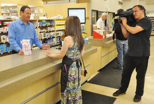 Geoff Barton (left), pharmacy manager at Madill's Drugs, assists a customer while cameraman Rob Gilfillan of Bamboo Shoots out of Saskatoon and Regina films the action.