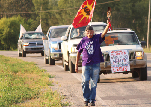 Emil Bell of Canoe Lake Cree Nation began a trek from Beauval to Saskatoon Aug. 26 to drum up support for a national inquiry into Canada's missing and murdered aboriginal women and girls. Here, Bell holds up a feather as he enters the Northern Village of Green Lake last Wednesday evening, Aug. 27.