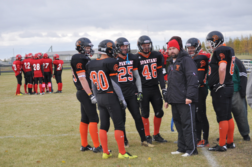 CHS Spartans head coach Craig Paylor discusses strategy with members of his team during the Oct. 2 home game against the Warman Wolverines.