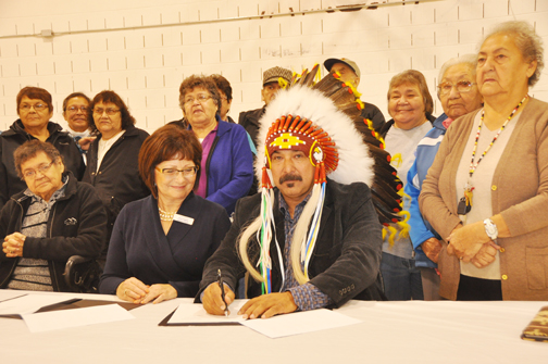 As a group of elders from Flying Dust First Nation look on, Flying Dust chief Robert Merasty and Vivian Pengelly, executive director of Habitat for Humanity Lloydminster, sign a memorandum of understanding Oct. 17 that marks the official agreement to develop an elders lodge on the reserve.