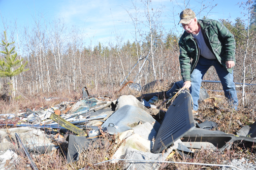 Meadow Lake area resident Maurice Demmans examines some of the garbage dumped on provincial Crown land west of the city. Demmans, who lives near the area in question, said he would like to see the illegal dumping stop.