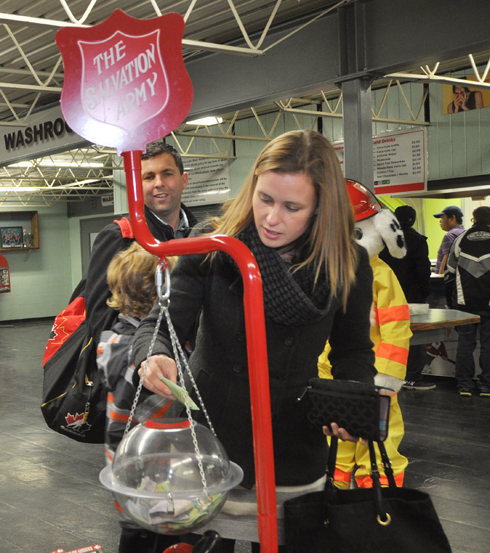 Trevor Gerwing looks on while his wife, Megan Gerwing, makes a cash donation to the Salvation Army's Christmas Kettle Campaign Nov. 21.