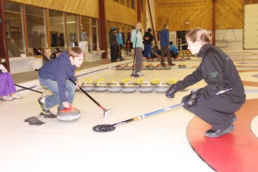 CHS Grade 12 student Andie Kurjata provides tips to junior curler Benjamin Spencer.