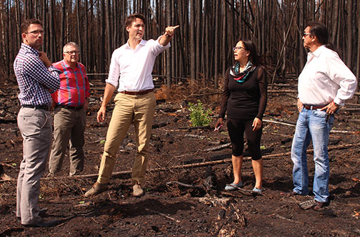 Federal Liberal leader Justin Trudeau – flanked by La Ronge mayor Thomas Sierzycki, Regina Liberal MP Ralph Goodale, Lac La Ronge Indian Band chief Tammy Cook-Searson and local candidate Lawrence Joseph – tours an area affected by recent wildfires.