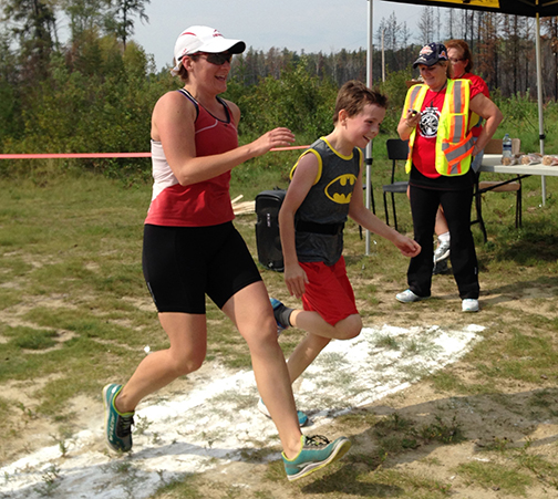 Stephanie Young (left) is a triathlete and one of the organizers of the 25th annual Freeze, Breeze and Wheeze triathlon held in La Ronge Aug. 30. Here, she accompanies Griffin Harrington across the finish line, as volunteer Connie McPhail clocks them in at 1:50:09.