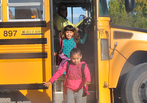 Students from across the region returned to class this week. Sept. 1 marked the first day of school for the 2015-16 academic year and children were all smiles as they anticipated a reunion with teachers and friends alike. Here, bus driver Jenay Gorst looks on as Grade 2 students Raelle Mitsuing (front) and Monique Aubichon depart the bus at Jubilee Elementary School Tuesday morning.